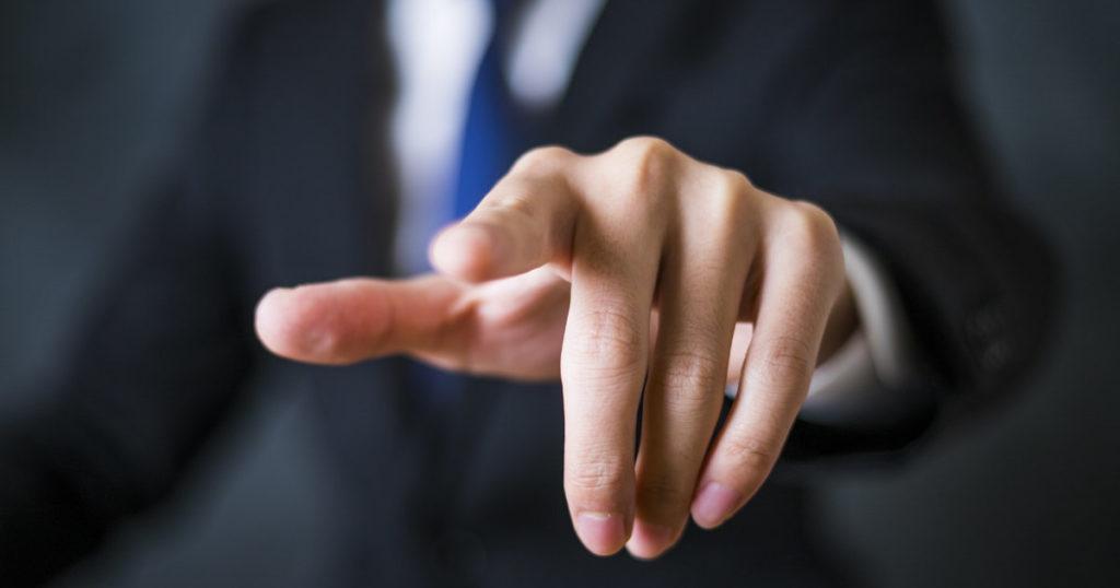 こちらに向かって人差し指を突き付けるスーツの男性