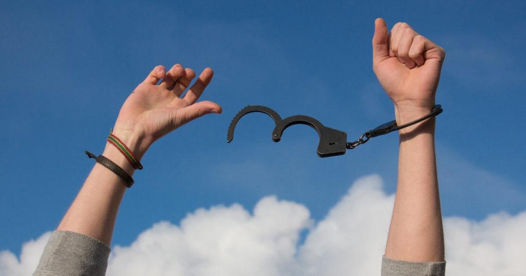 青空に掲げられた両手と、外された手錠