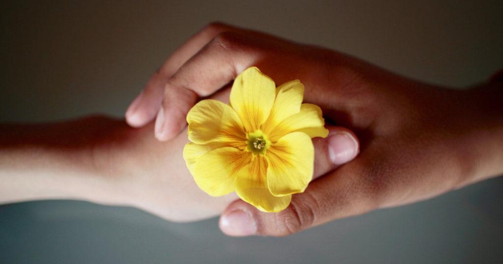 花を持つ二人の手